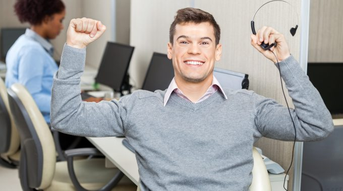 Successful Customer Service Representative With Arms Raised Holding Headset In Office